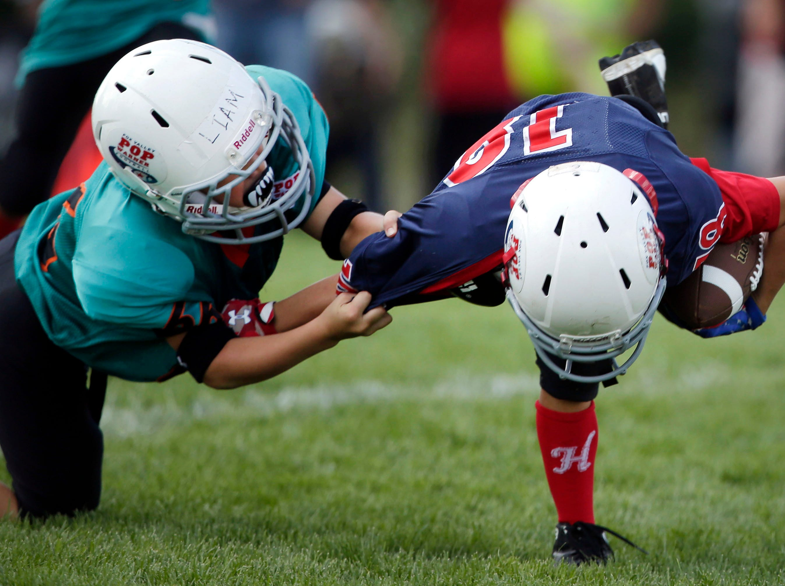 Liam Kelley of the Rockets tackles a Patriots player as Fox Valley Pop Warner Football opens the season Saturday, September 8, 2018, at Plamann Park in Grand Chute, Wis.