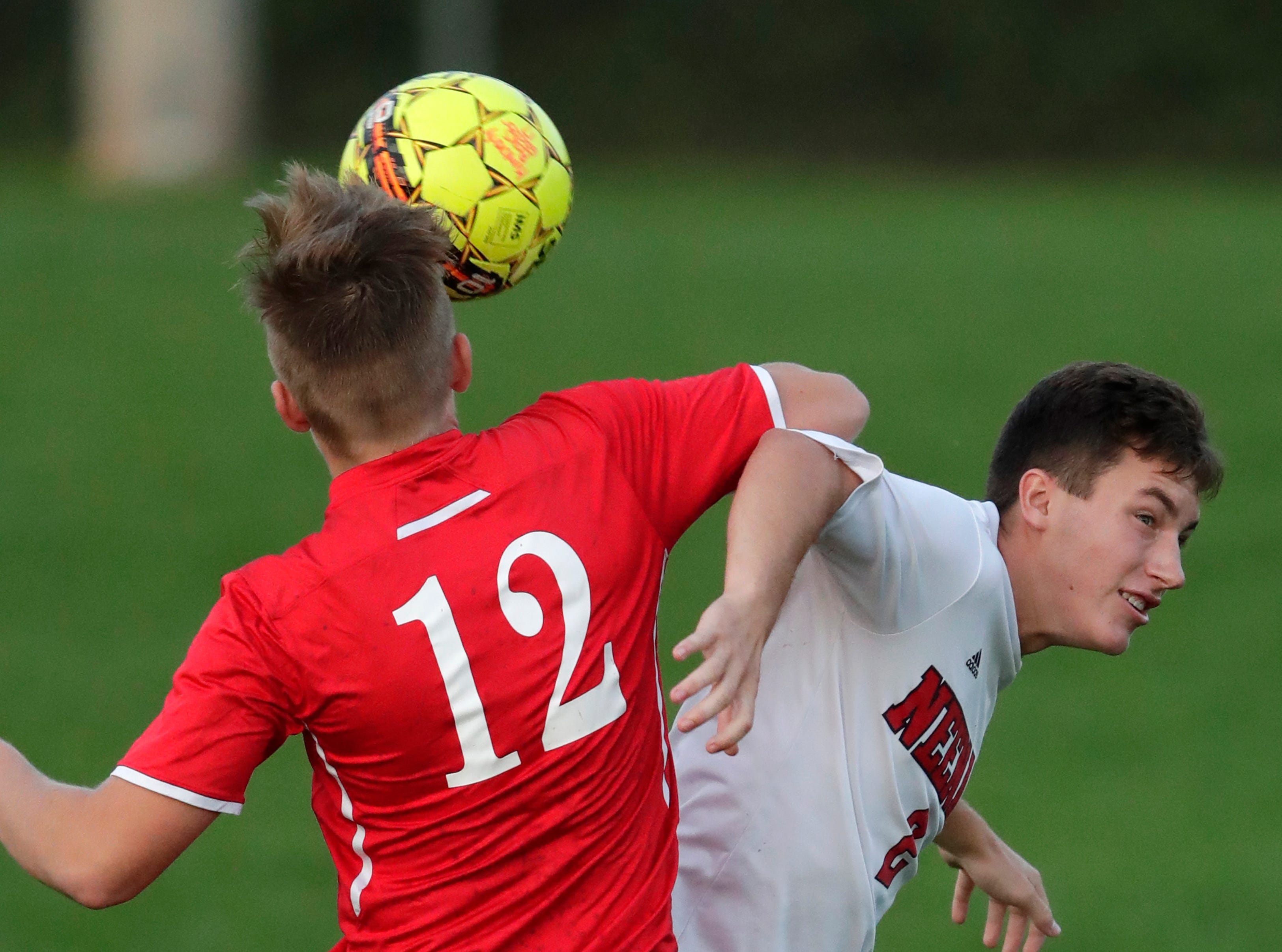 Kimberly High School's Nick Riffe (12) goes up against Neenah High School's Thomas Priest (2) during their boys soccer game Tuesday, Sept. 4, 2018, at Papermaker Field in Kimberly, Wis. 
