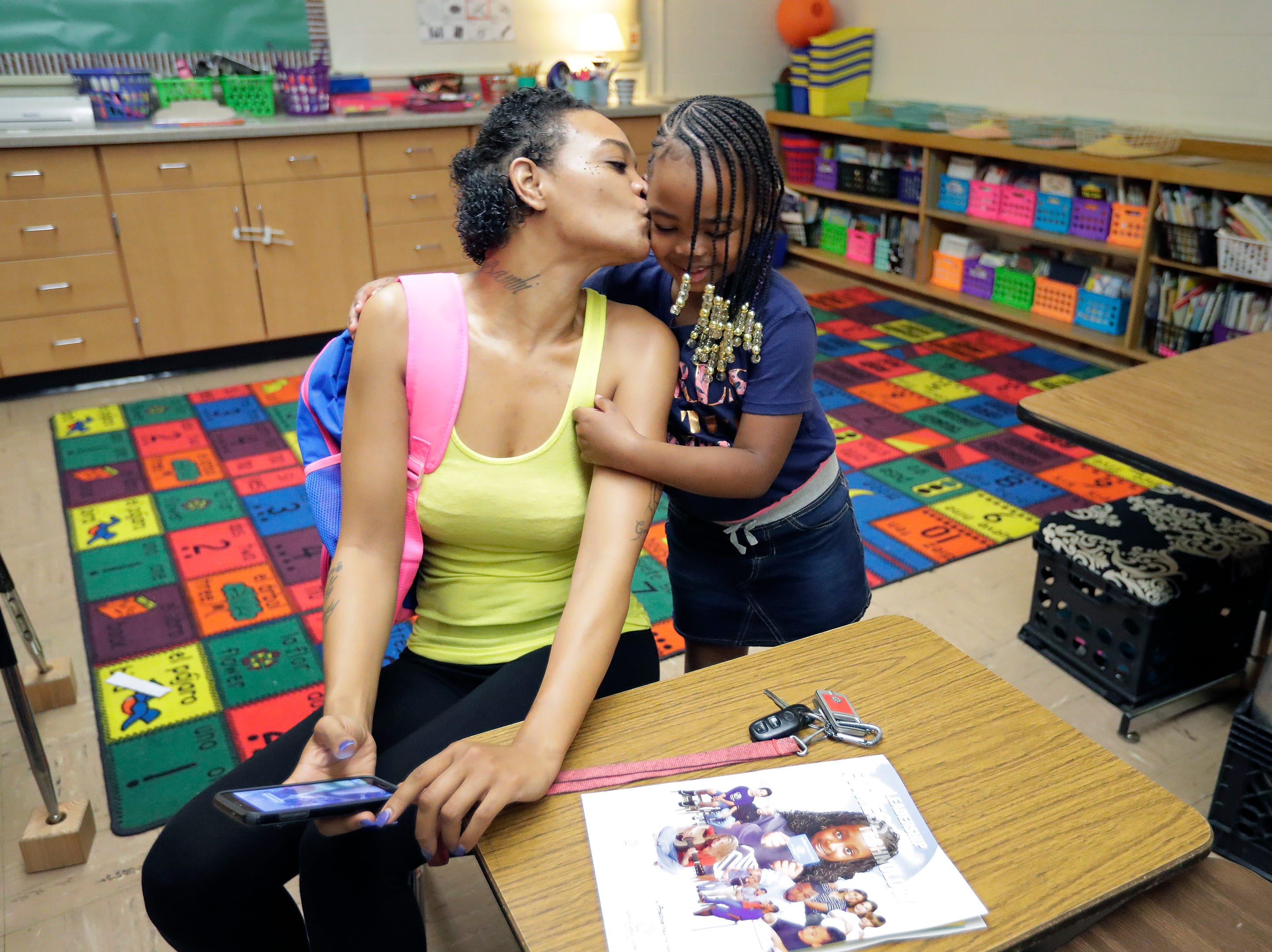 Jessica Terry, left, kisses her daughter Jalayah West, 6, as gets ready to join her first grade classmates on the first day of school Tuesday, Sept. 4, 2018, at Badger Elementary School in Appleton, Wis. 