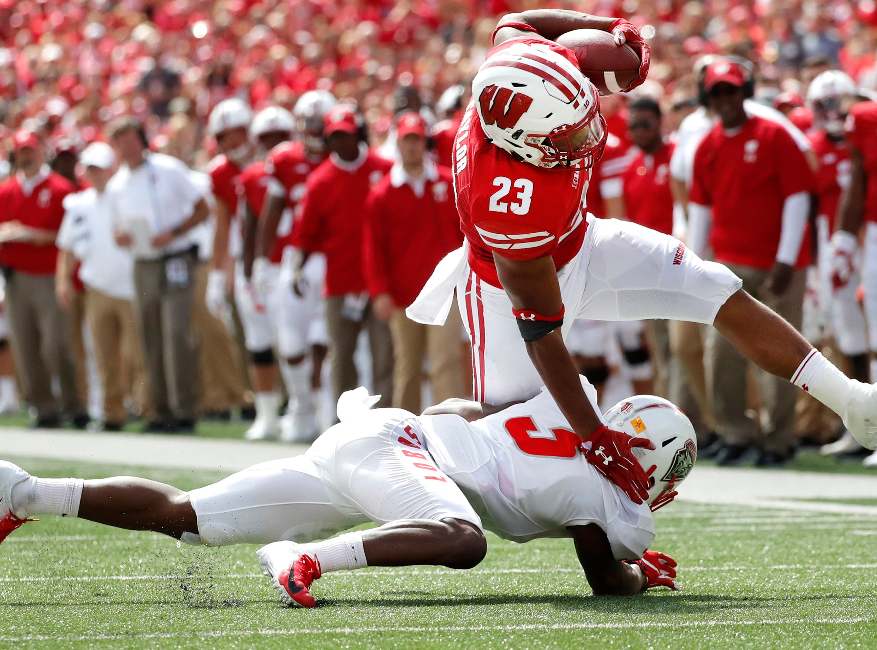 Wisconsin running back Jonathan Taylor (23) stretches for more yards while being brought down by New Mexico safety Michael Sewell Jr. (5) Saturday, Sept. 8, 2018, at Camp Randall Stadium in Madison, Wis.