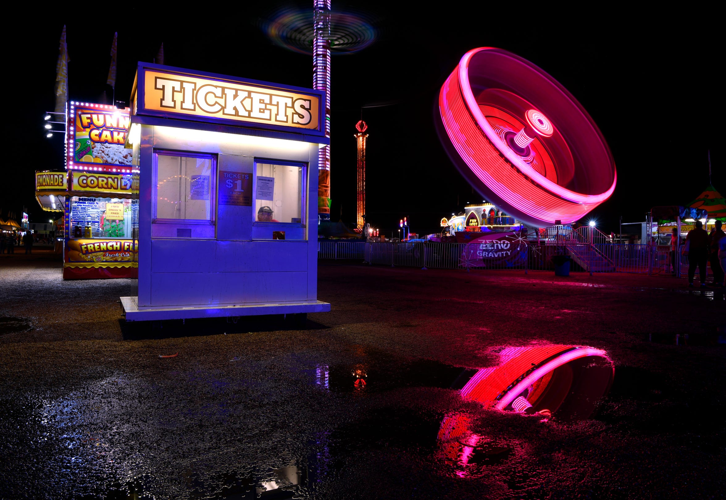 A salesman sits in the window of a ticket booth at the West Texas Fair & Rodeo Thursday Sept. 6, 2018 as the Zero Gravity ride spins in the background. The motion of the attraction and its colored lights created this blurred image thanks to a long exposure.