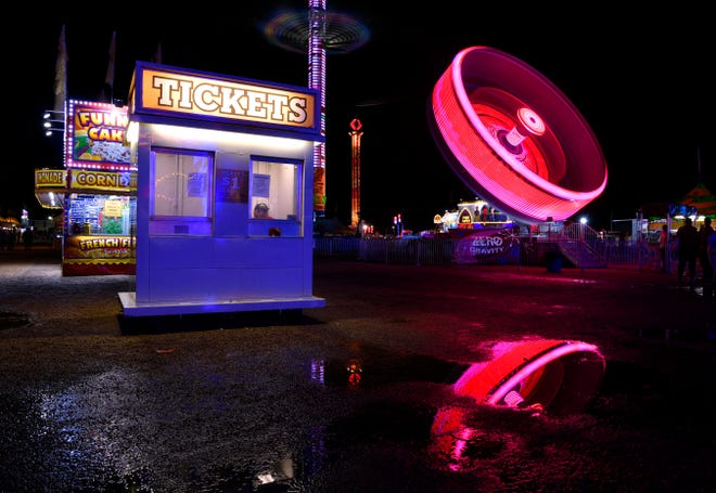 A salesman sits in the window of a ticket booth at the West Texas Fair & Rodeo Thursday as the Zero Gravity ride spins in the background. The motion of the attraction and its colored lights created this blurred image thanks to a long exposure.