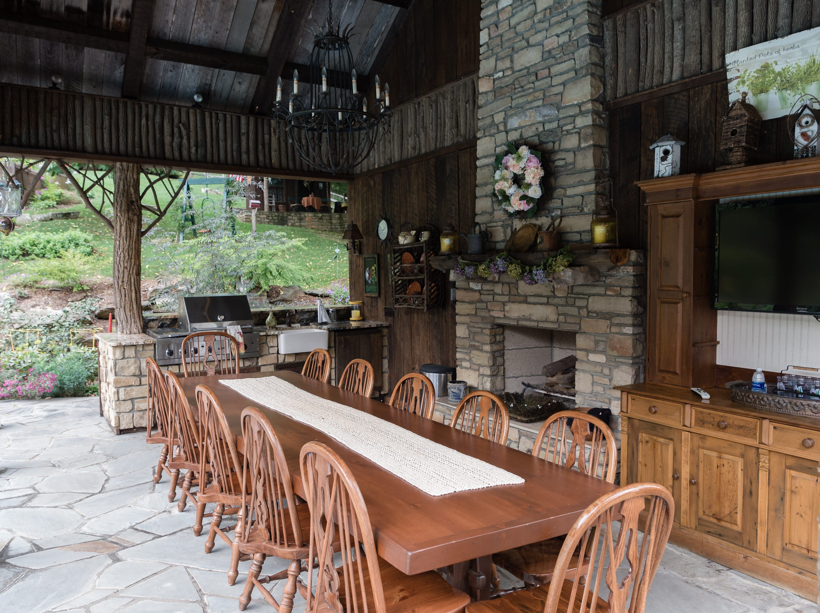 A covered outdoor dining area in the backyard of Dan and Belle Fangmeyer's log cabin in Waynesville.