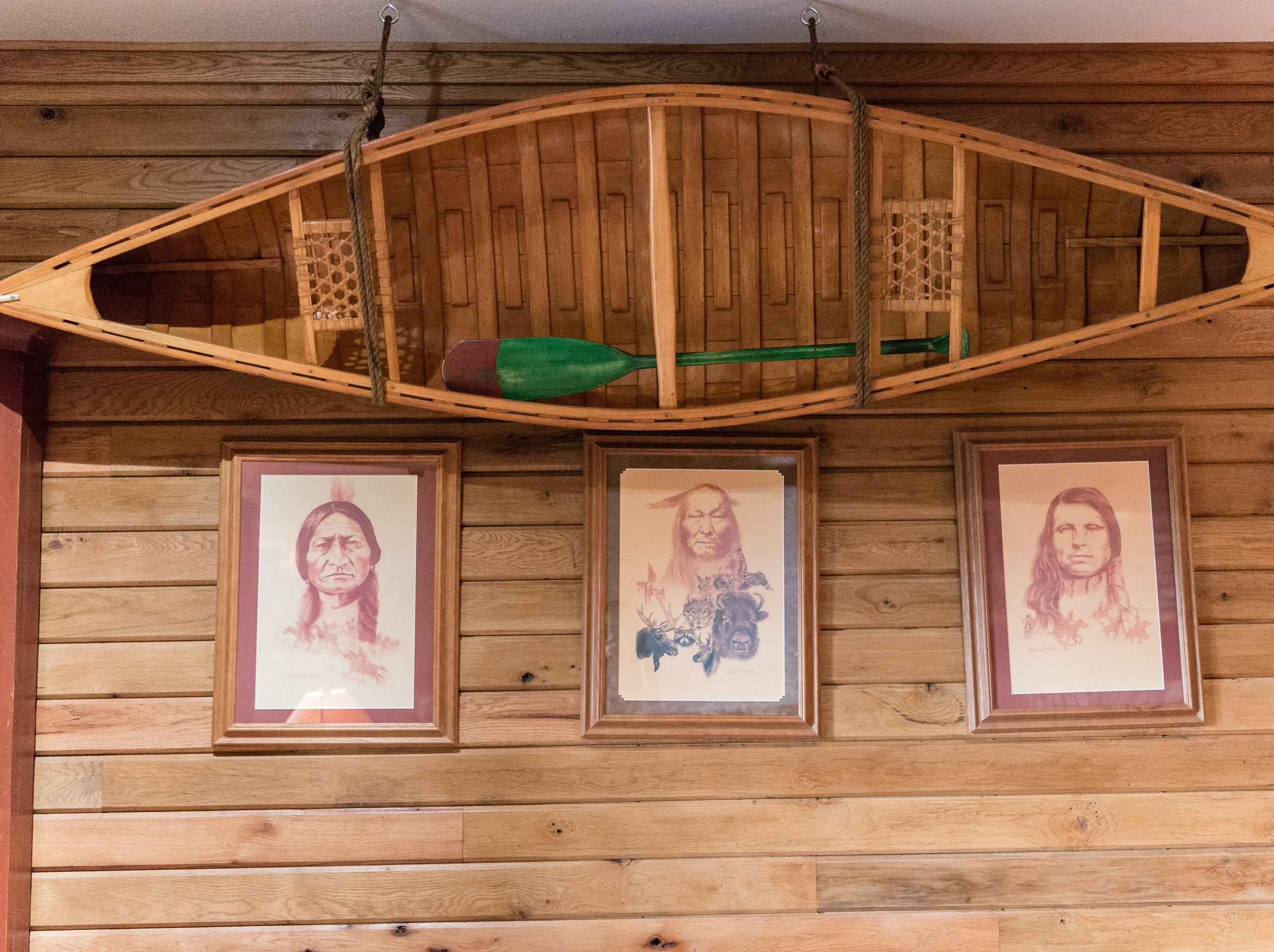 A wooden canoe hanging over three portraits of Native Americans in Dan and Belle Fangmeyer's log cabin in Waynesville.
