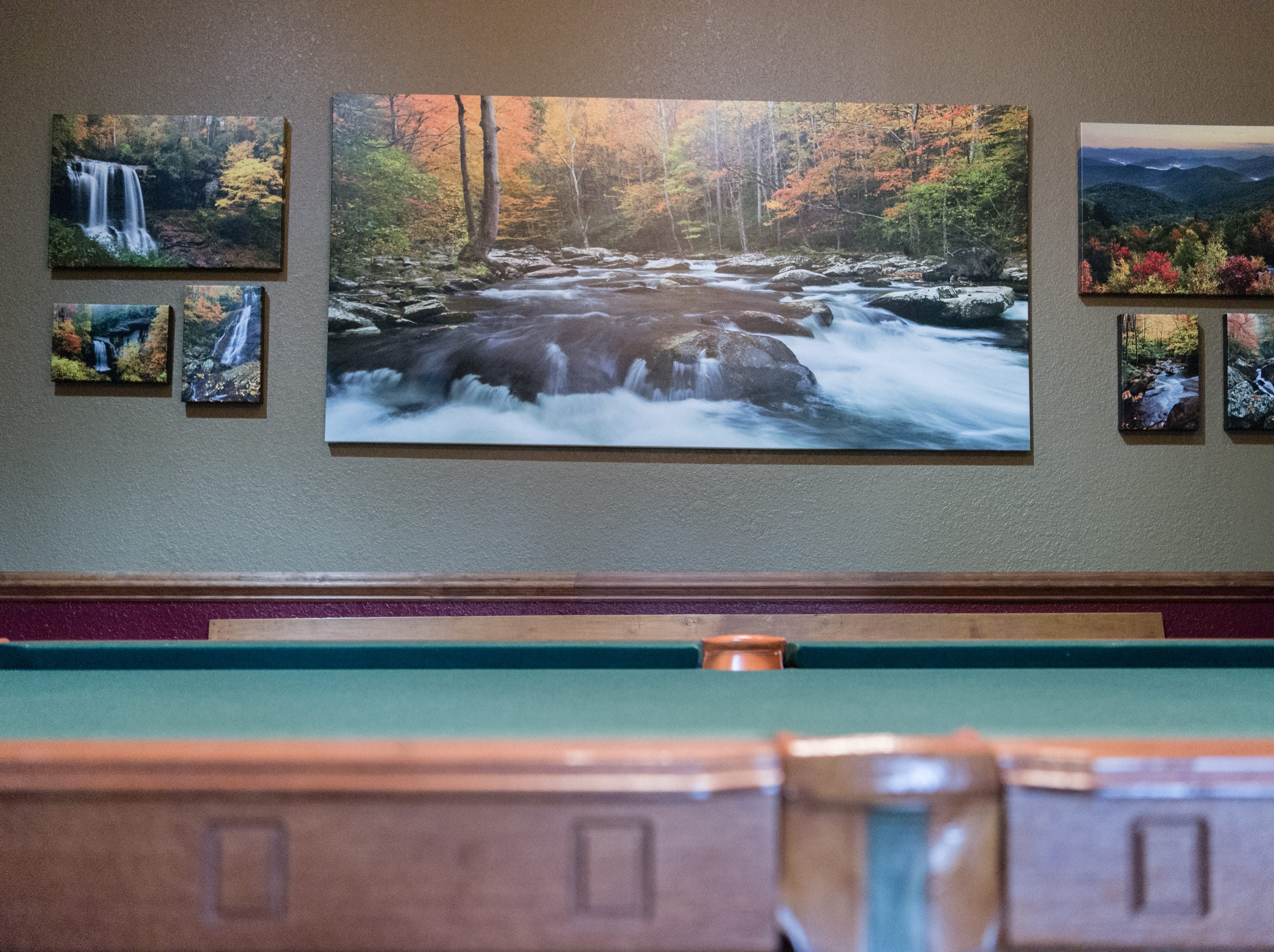 Photographs in a game room on the basement level of Dan and Belle Fangmeyer's log cabin in Waynesville.