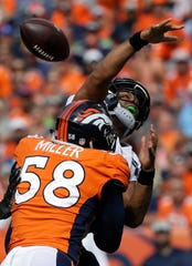 Seattle Seahawks quarterback Russell Wilson loses the ball as he is hit by Denver Broncos linebacker Von Miller (58). The Seahawks recovered the ball on the play.