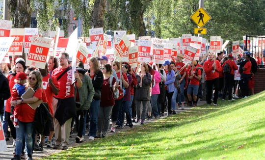 Striking teachers march around the Tacoma School District Central Administration Building, Monday, Sept. 10, 2018, in Tacoma, Wash. Teachers in the district have been on strike since last week.