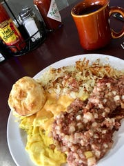 Daddy O's in Port St. John serves a lot of food, like this pile of crisp hash browns, a lot of corned beef hash, nicely scrambled eggs with chees and a biscuit.