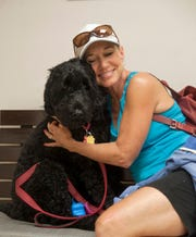 Marsha Gernhardt of Marlton hugs her Portuguese Water Dog named Murphy at the Mount Laurel Animal Hospital.