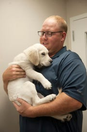 Ted Fitzpatrick of Delran holds his English Cream Golden Retriever named Bailey during a visit to the Mount Laurel Animal Hospital.