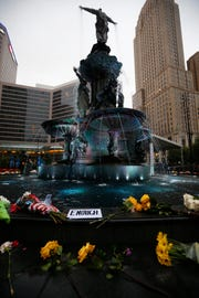 Flowers and notes are left at the Tyler Davidson Fountain at Fountain Square Sept. 10, 2018, four days after a gunman killed three people and shot two others last Thursday at Fifth Third Center at Fountain Square.