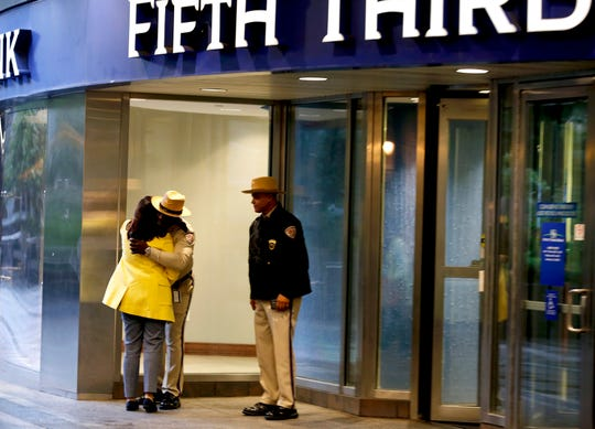Kim Halbauer, director of private banking for Fifth Third, hugs security guard Ray Jackson, left, and Estill Word as bank employees returned to work four days after a Sept. 6, 2018 mass shooting in the lobby at the Fifth Third Center in Downtown Cincinnati.