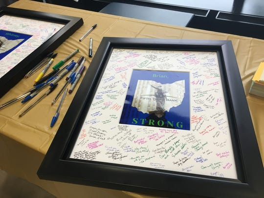"""As Fifth Third employees entered work this morning they could sign framed prints with the word """"STRONG"""" under the outline of the state of Ohio and Genius of Water statue."""