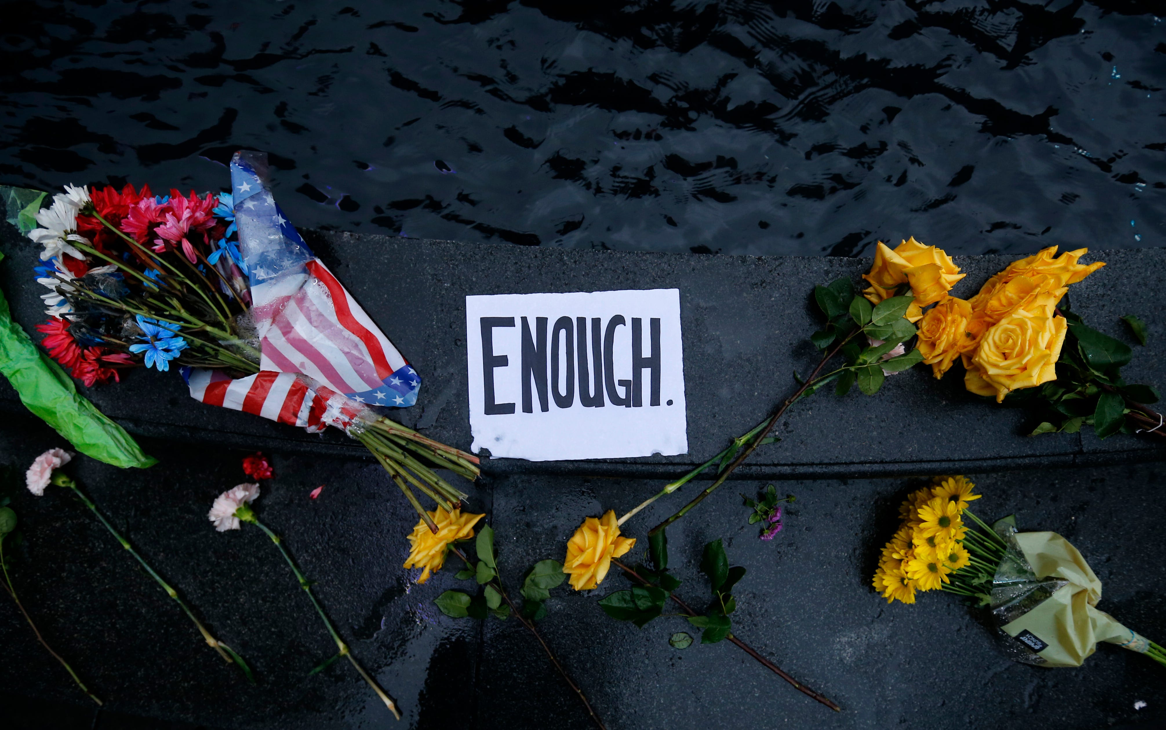 Flowers and notes are left at the Tyler Davidson Fountain at Fountain Square, after a gunman killed three people and shot two others last Thursday at Fifth Third Center at Fountain Square. Photo shot Monday, September 10, 2018.