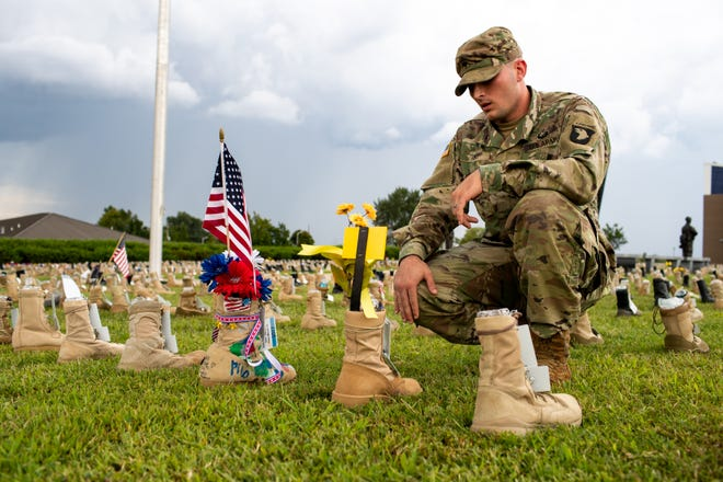 Specialist Allen Hunt Jr. takes a breath as he stares at his friend's boot at the Boots on the Ground display outside of 101st Airborne Division Headquarters at Fort Campbell Friday, Sept. 7, 2018, in Ky. Over 7,000 boots were displayed to honor service members who have died since the 9/11 attacks.