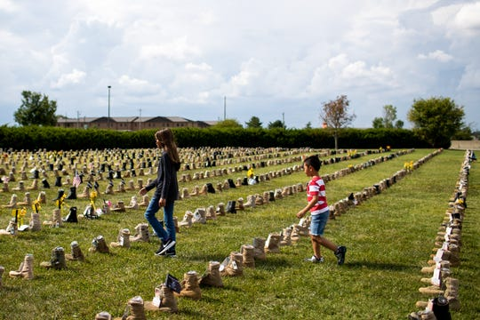 Micah Javillo, 5, follows his sister Maia Javillo, 11, as they walk through the Boots on the Ground display outside of 101st Airborne Division Headquarters at Fort Campbell Friday, Sept. 7, 2018, in Ky. Over 7,000 boots were displayed to honor service members who have died since the 9/11 attacks.
