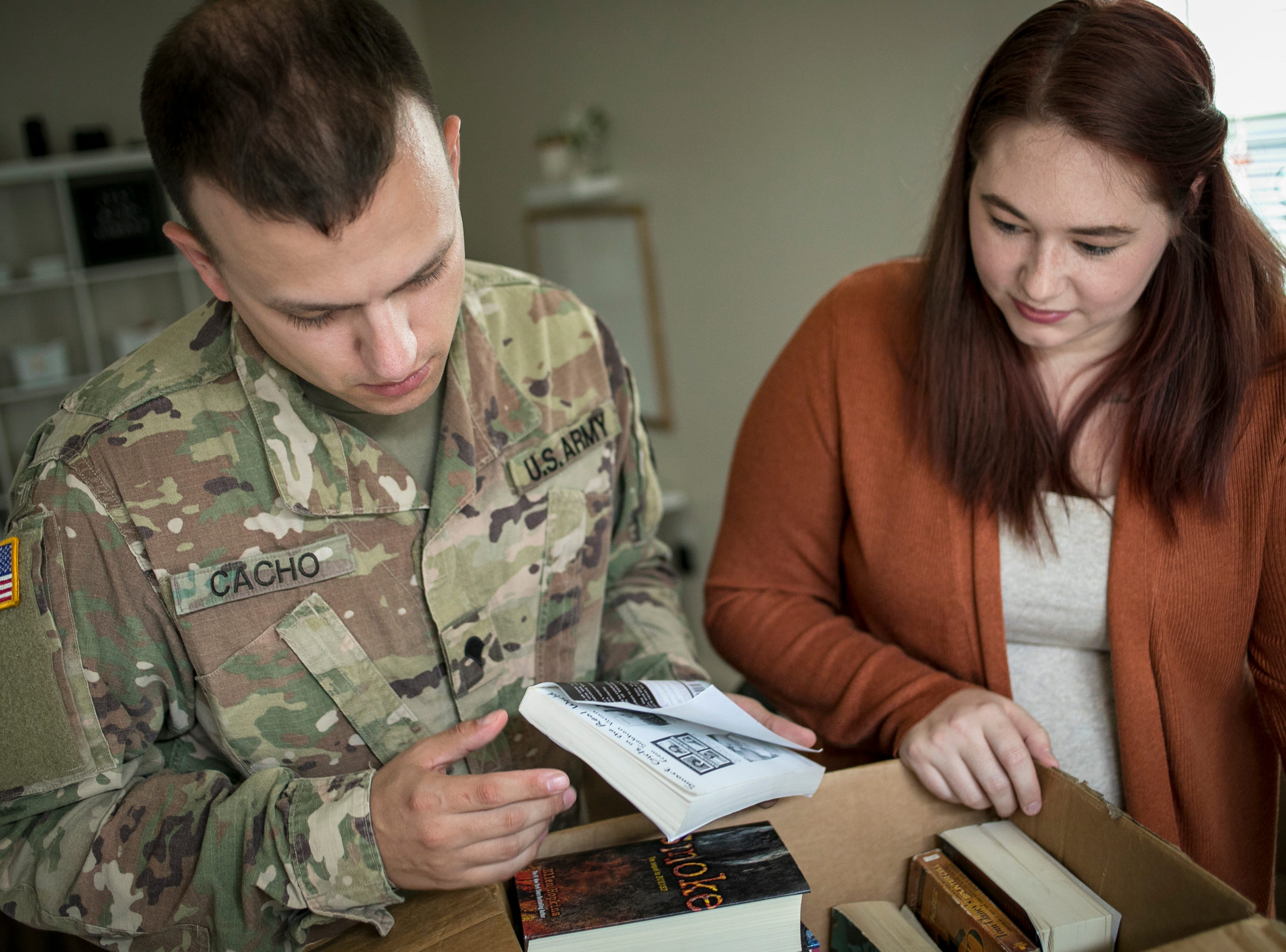 Specialist Christopher Cacho and his wife Andrea look through their damaged books after a bad experience moving from Ft. Campbell to Ft. Belvoir back in July. Many of their pieces of furniture were scratched and damaged. Books had water damage, including a family Bible. But the worst may have been the wedding rings that disappeared. September 4, 2018.