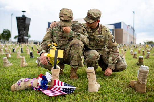Pfc. Crisstopher Hayward wraps his arm around Specialist Allen Hunt Jr. (left) as he wipes his eyes in front of their friend's boot at the Boots on the Ground display outside of 101st Airborne Division Headquarters at Fort Campbell Friday, Sept. 7, 2018, in Ky. Over 7,000 boots were displayed to honor service members who have died since the 9/11 attacks.