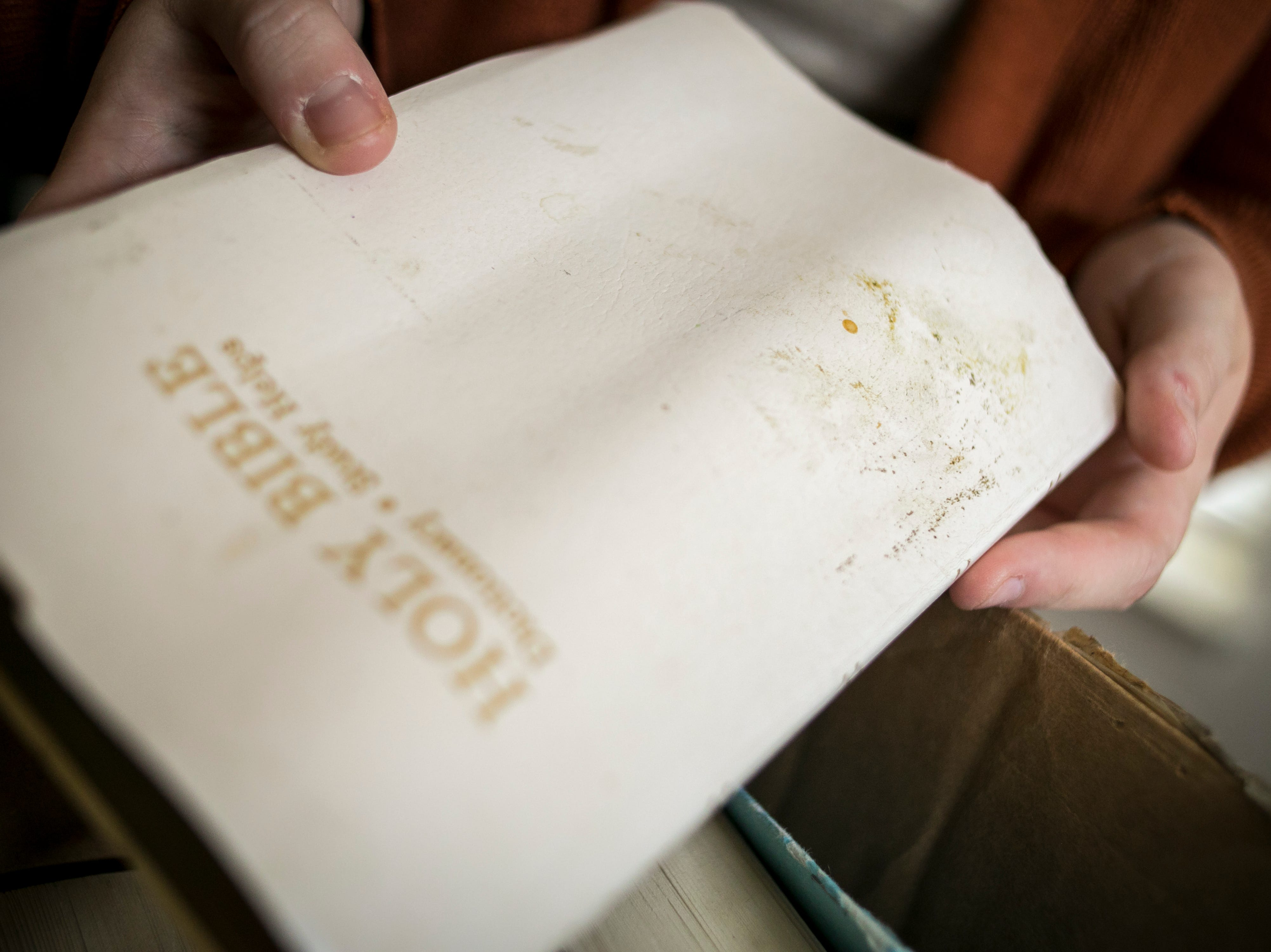 Andrea Cacho examines a water-damaged family Bible, after a bad experience moving from Ft. Campbell to Ft. Belvoir back in July. September 4, 2018.