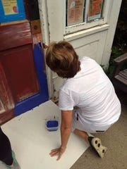 Supporters of the Watchung Library sanded and painted its front door purple on Saturday, Sept. 8.