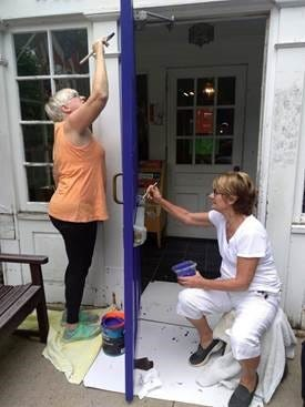 Angela Della Ventura, right, and Gail Trafaro paint the front door of the Watchung Library on Saturday.