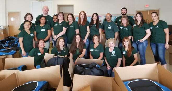 Peapack-Gladstone Bank employees sort and pack incoming school supply donations at the United Way of Northern New Jersey consolidation site in Somerville.
