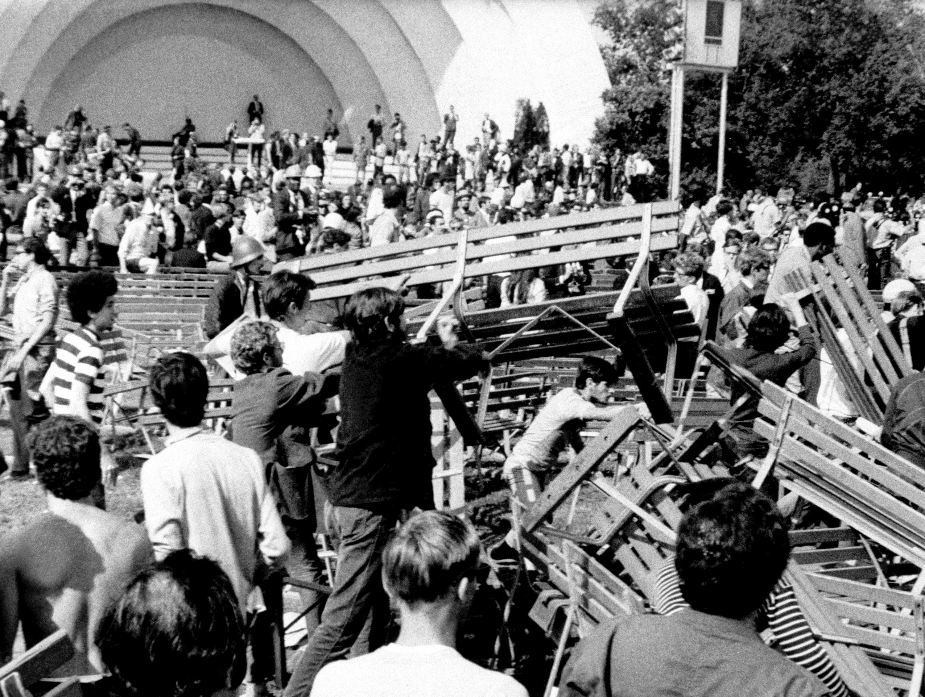 Demonstrators use park benches at Grant Park's Band Shell to construct a barricade against Chicago police and National Guardsmen in Chicago on August 28, 1968. The confrontation left many injured and arrested.