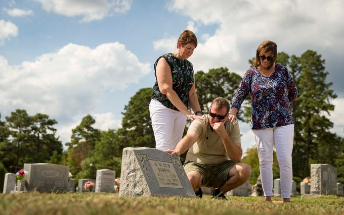 "Children of A.W. ""Dub"" Barron, Connie Hoye, left, Wade Mulligan, kneeling, and Lori Stangl at the grave site of Barron, Saturday, Sept. 1, 2018, in Tyler, Texas. Mulligan was seeing the grave site of his father for the first time."