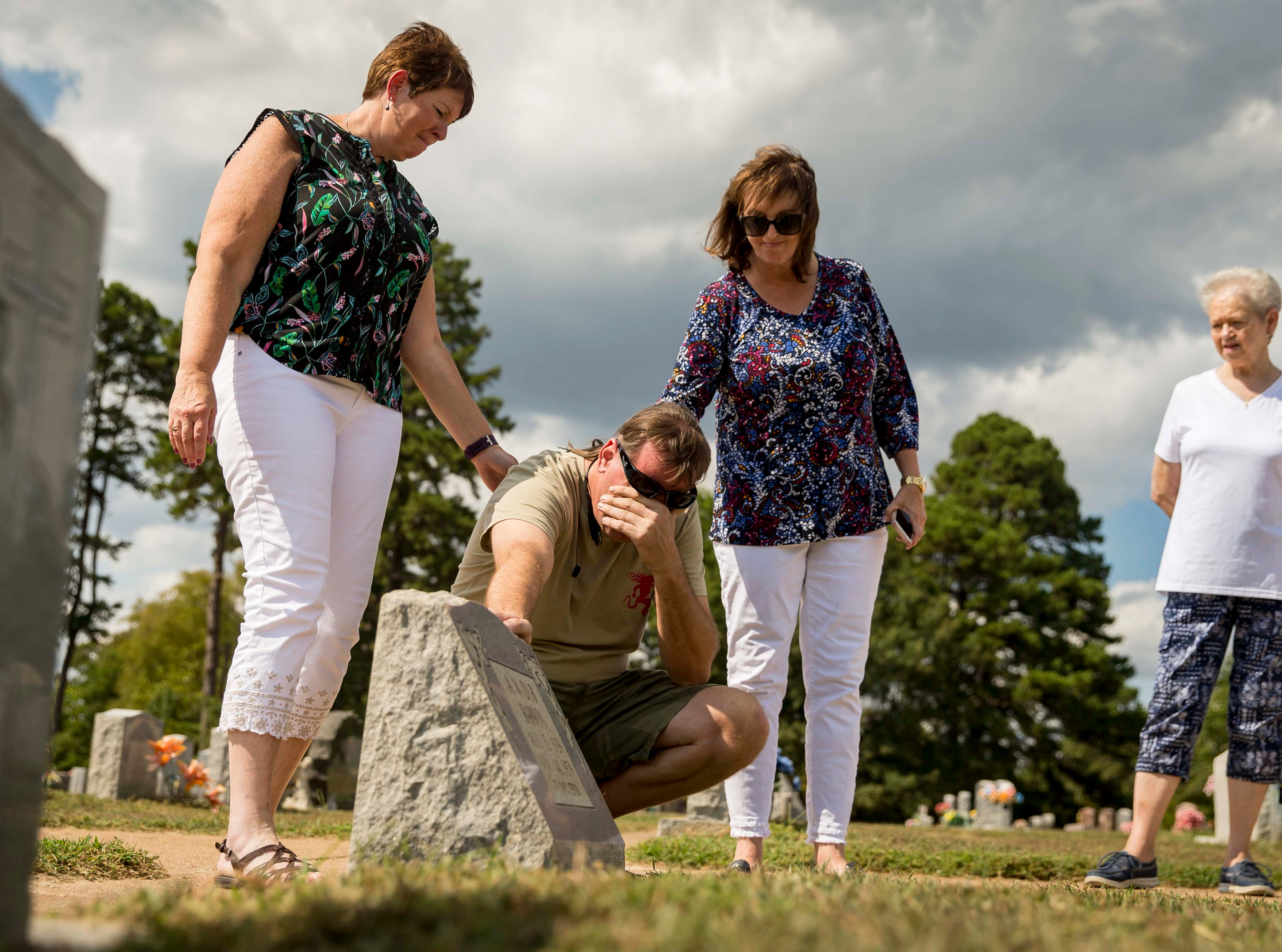 "Children of A.W. ""Dub"" Barron Connie Hoye, left, Wade Mulligan, kneeling, and Lori Stangl at the gravesite of Barron, Saturday, Sept. 1, 2018, in Tyler, Texas. Mulligan was seeing the gravesite of his father for the first time."