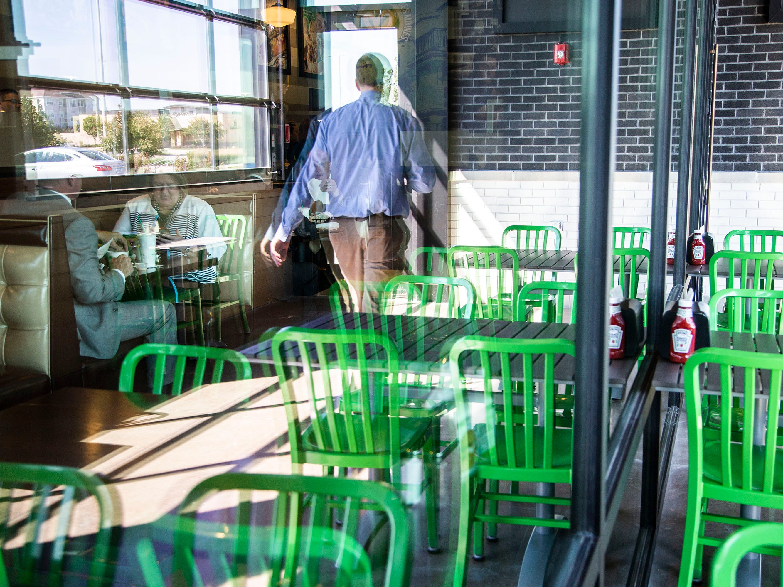 Guests dine on burgers and other food from Iowa's first Wahlburgers restaurant before it's official opening on Monday, Sept. 10, 2018, in the Jordan Creek Town Center in West Des Moines.