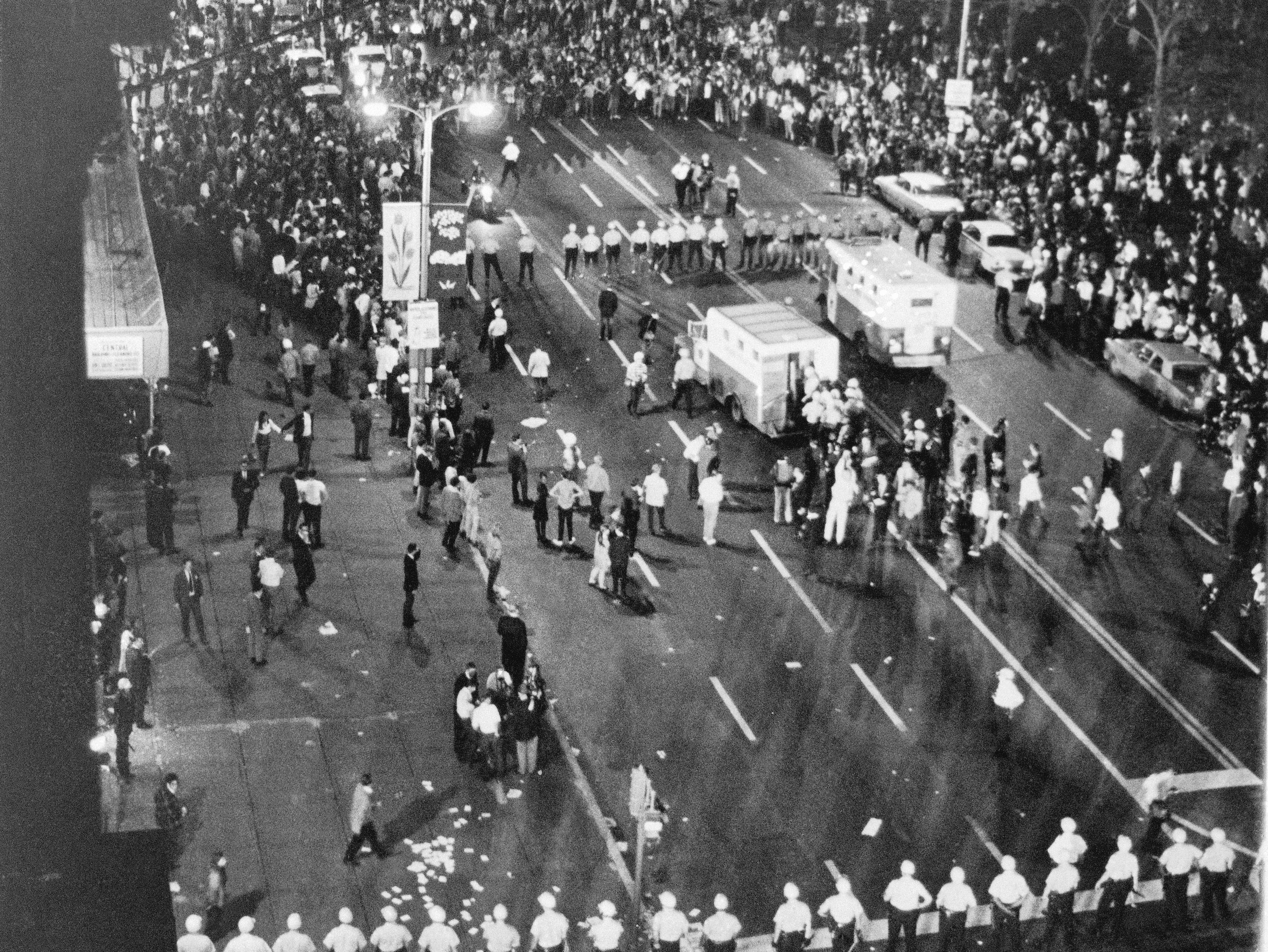 As demonstrators are placed into police vans, Chicago police form a battle line against thousands of others during a melee in Chicago on Aug. 28, 1968. The police are lined up and looking north on Michigan Avenue at the Conrad Hilton hotel, the headquarters for the Democratic National Convention.
