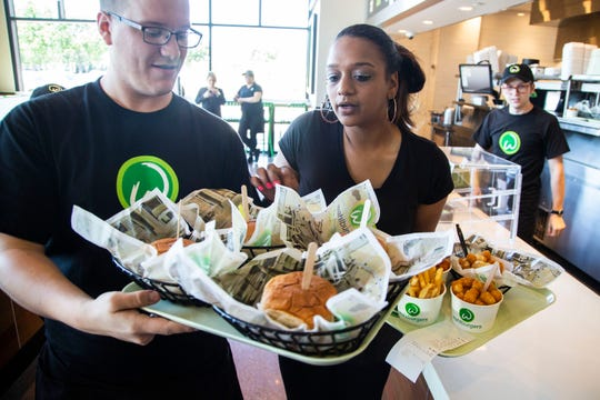 Two Wahlburgers servers carry trays of hamburgers, fires and tater tots out to customers on Monday, Sept. 10, 2018, at the burger restaurant in the Jordan Creek Town Center in West Des Moines.