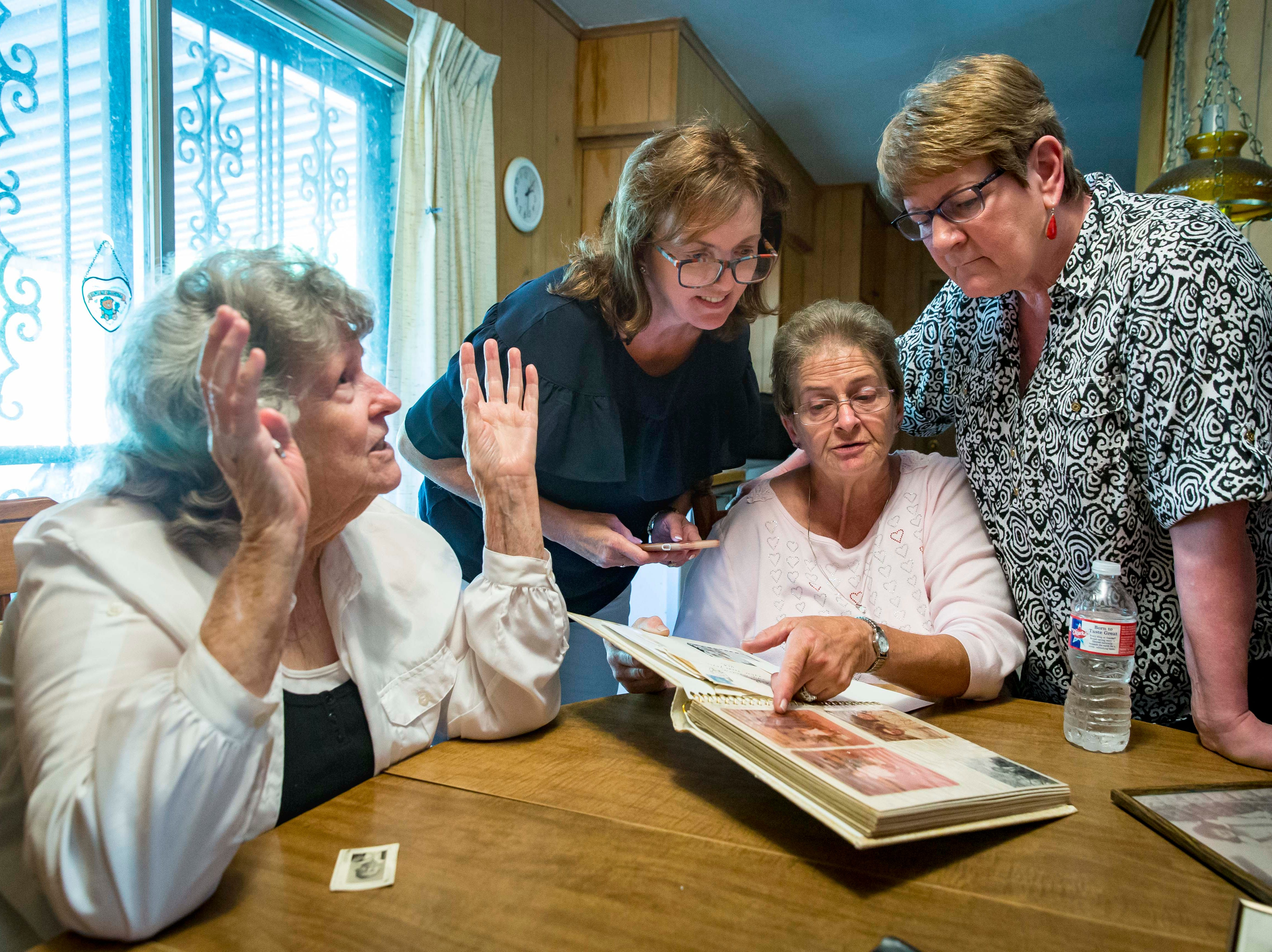 "Hellen Sexton, left, looks over photo albums with children of A.W. ""Dub"" Barron at a family reunion in Tyler, Texas, Sunday, Sept. 2, 2018, in Tyler, Texas. Lori Stangl of Omaha, Nebraska, standing, left with glasses, Dena Simon, pointing, of Delmont, Pennsylvania, with her half-sister Linda."