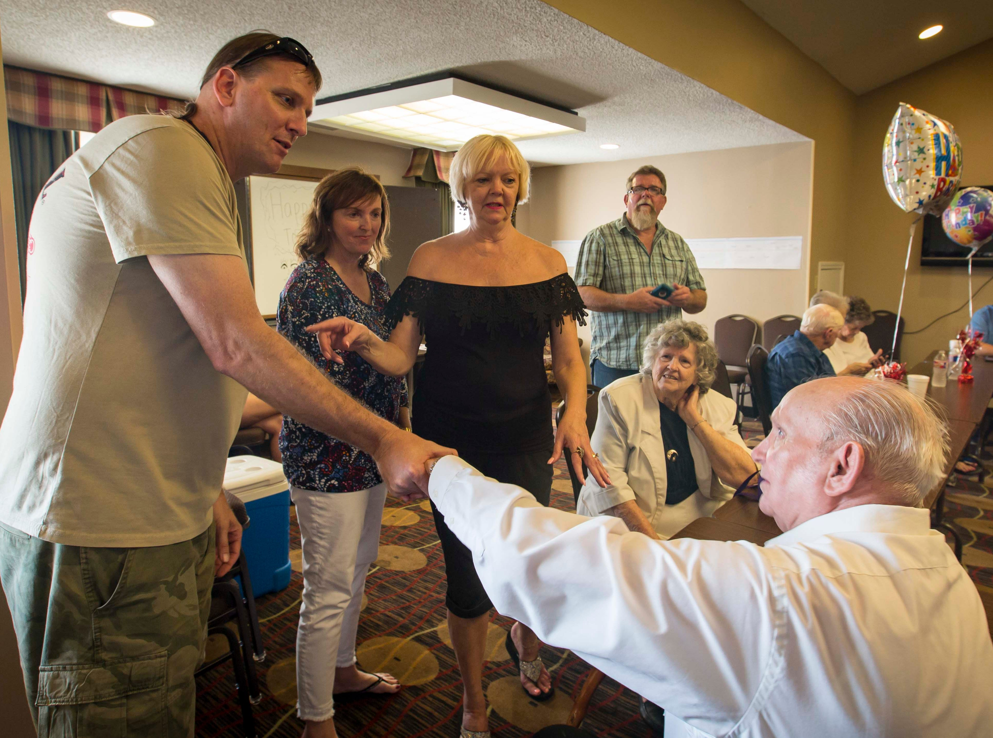 Wade Mulligan of Las Vegas, left, greets his half-uncle Bobby Sexton at a family reunion in Tyler, Texas, Saturday, Sept. 1, 2018, in Tyler, Texas. At center are two of Mulligan's half-sisters, Lori Stangl and Shelia Barron Jenkins.