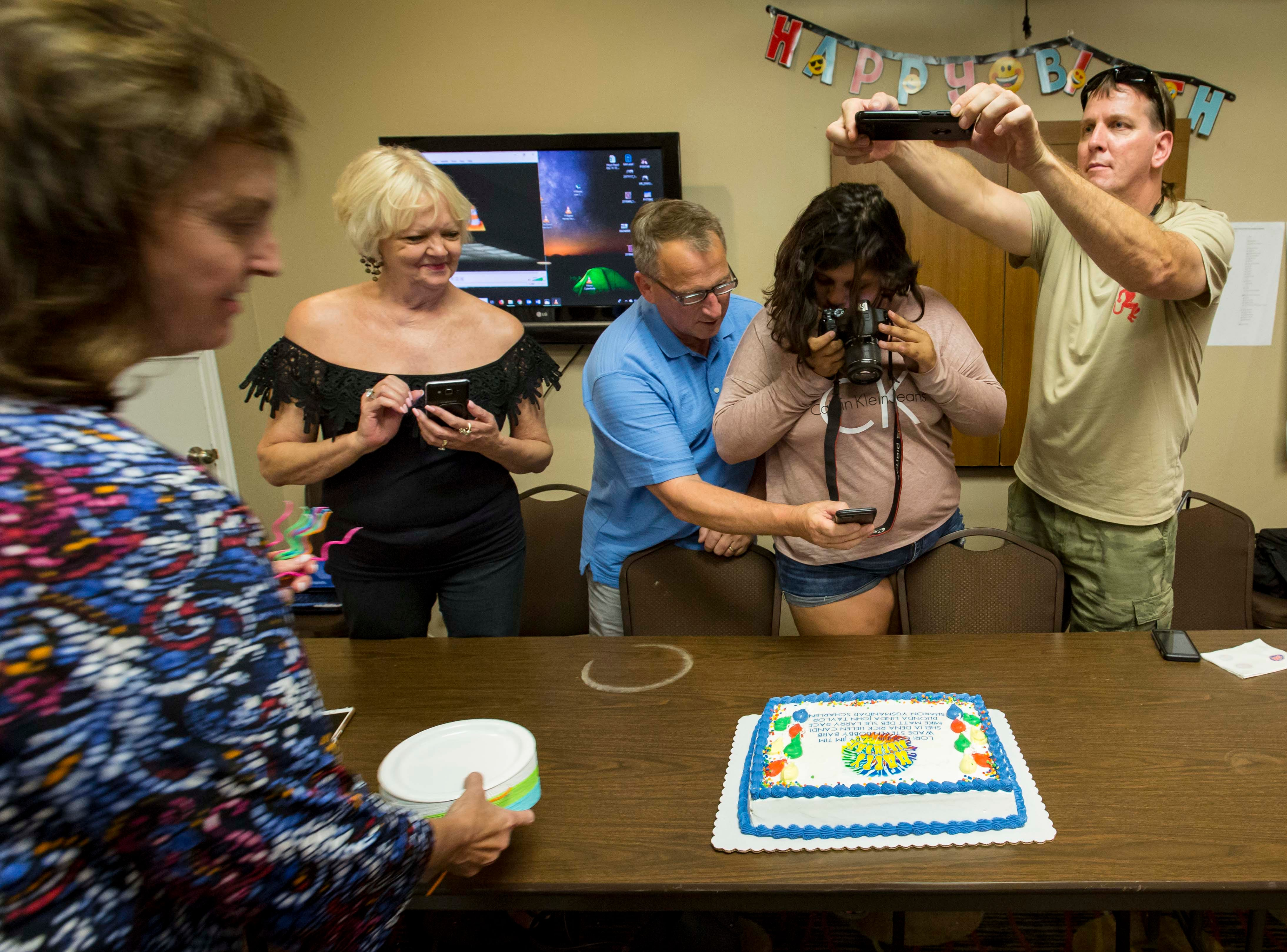 "The adult children of A.W. ""Dub"" Barron and their family members take photos of a birthday cake at a family reunion in Tyler, Texas, Saturday, Sept. 1, 2018. The cake had the names of the known children fathered by Barron until his death in 1979, giving everyone a chance to share a birthday together as brothers and sisters."