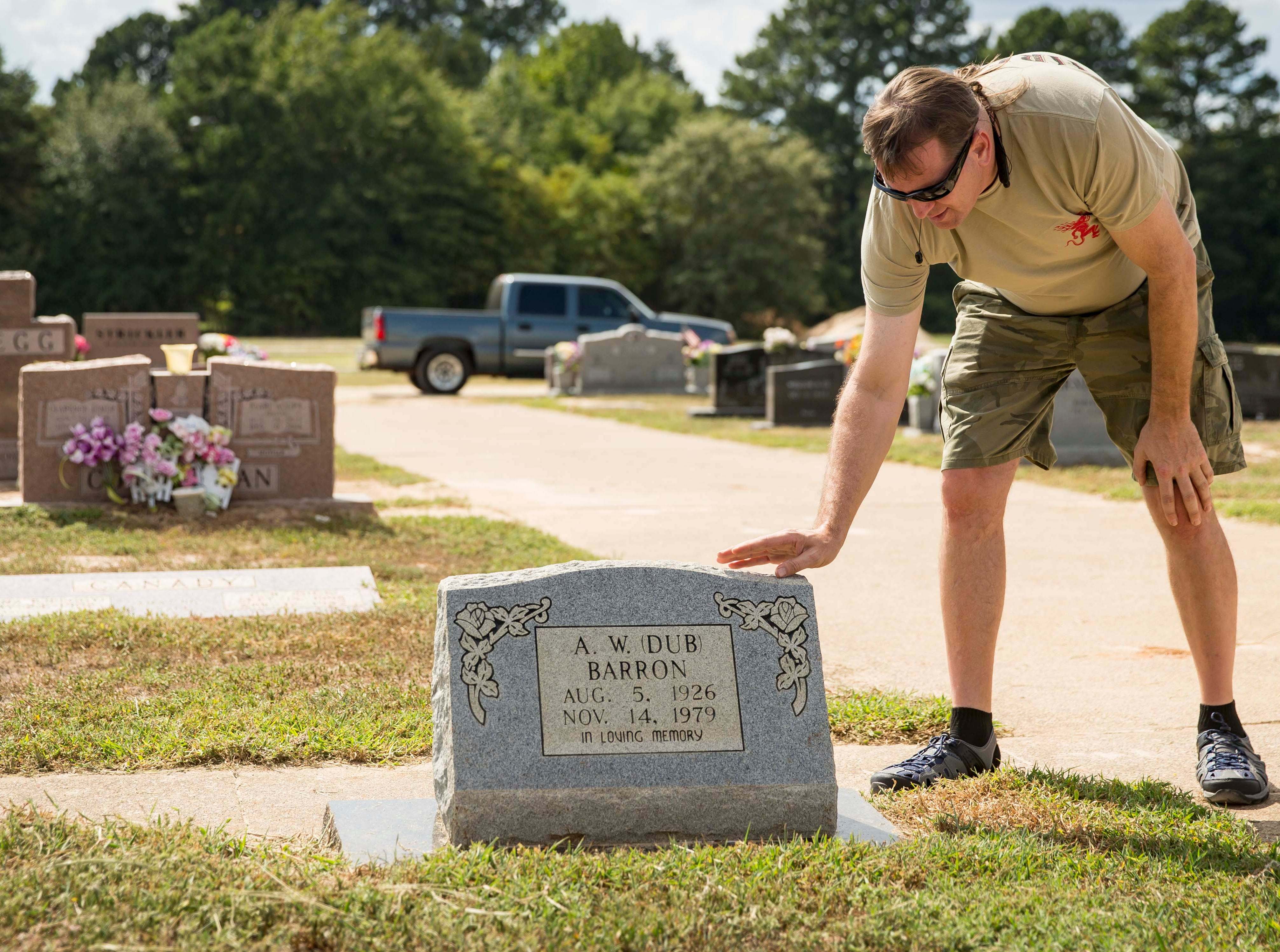 "Wade Mulligan touches the stone at the gravesite of A.W. ""Dub"" Barron, Saturday, Sept. 1, 2018, in Tyler, Texas. Mulligan was seeing the gravesite of his father for the first time during a reunion of Barron's known children."
