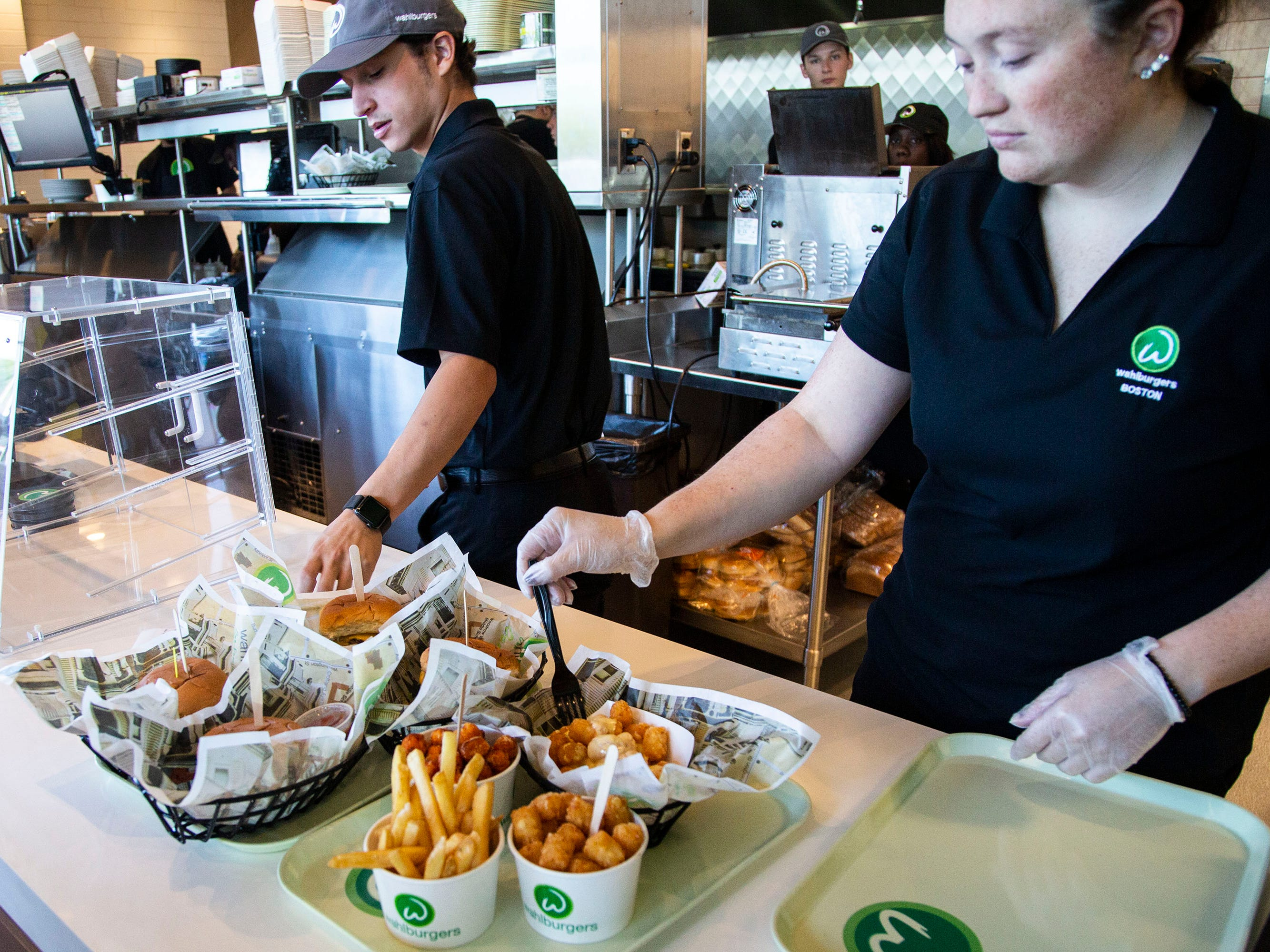 The Wahlburgers staff prepares for opening day of the restaurant this week during a preview event for Hy-Vee employees on Monday, Sept. 10, 2018, in the Jordan Creek Town Center in West Des Moines. Hy-Vee plans to bring 26 locations of the burger restaurant to the midwest.
