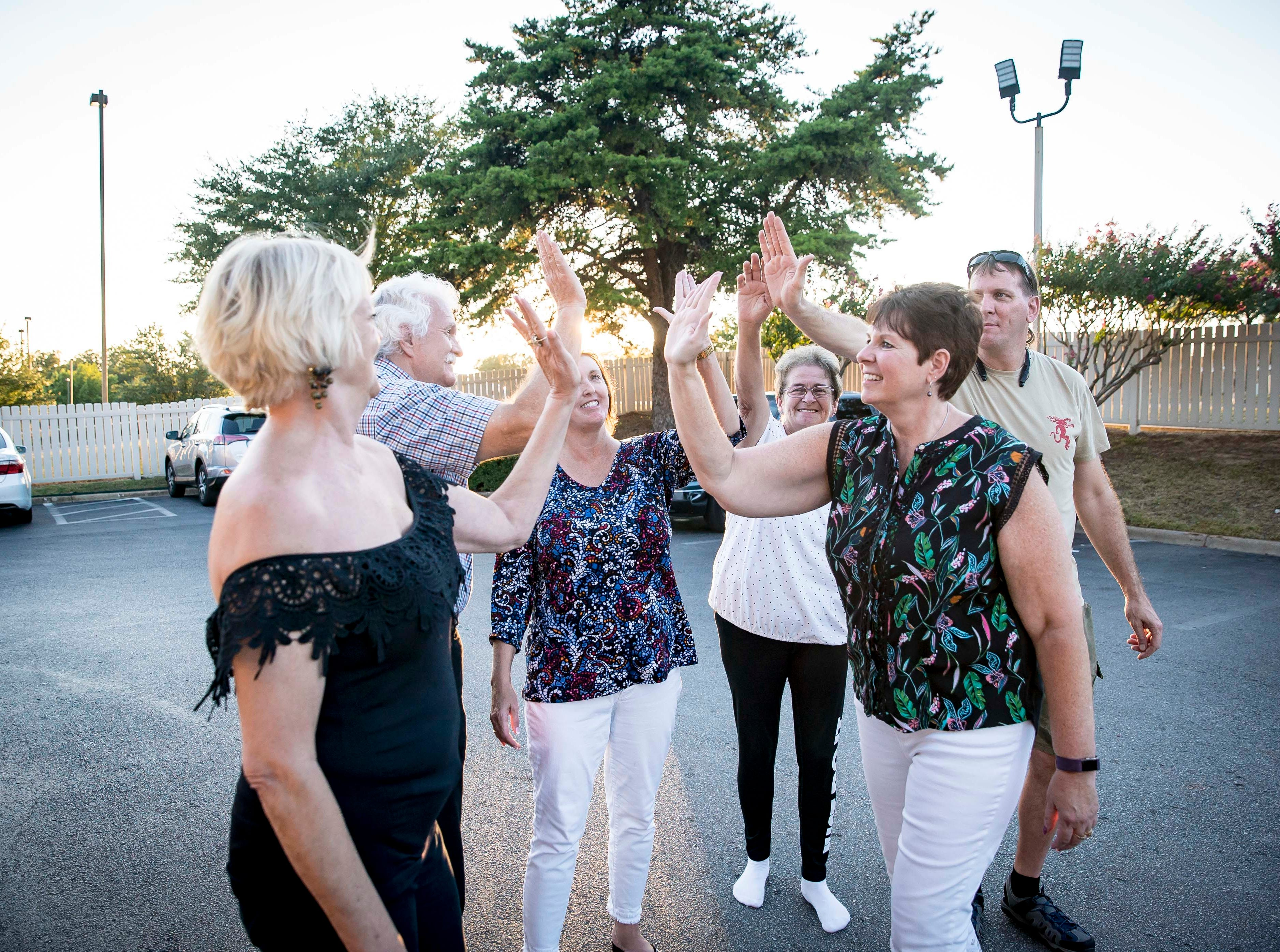 "Adult children of A.W. ""Dub"" Barron high-five after a group photo during family reunion Saturday Sept. 1, 2018, in Tyler, Texas. Shelia Jenkins, left, of Dallas, Texas, Michael Banks of Des Moines, Iowa, Lori Stangl of Omaha, Nebraska,Dena Simon of Delmont, Pennsylvania, Connie Hoye of Kansas City, Missouri, and Wade Mulligan, right, of Las Vegas, Nevada."