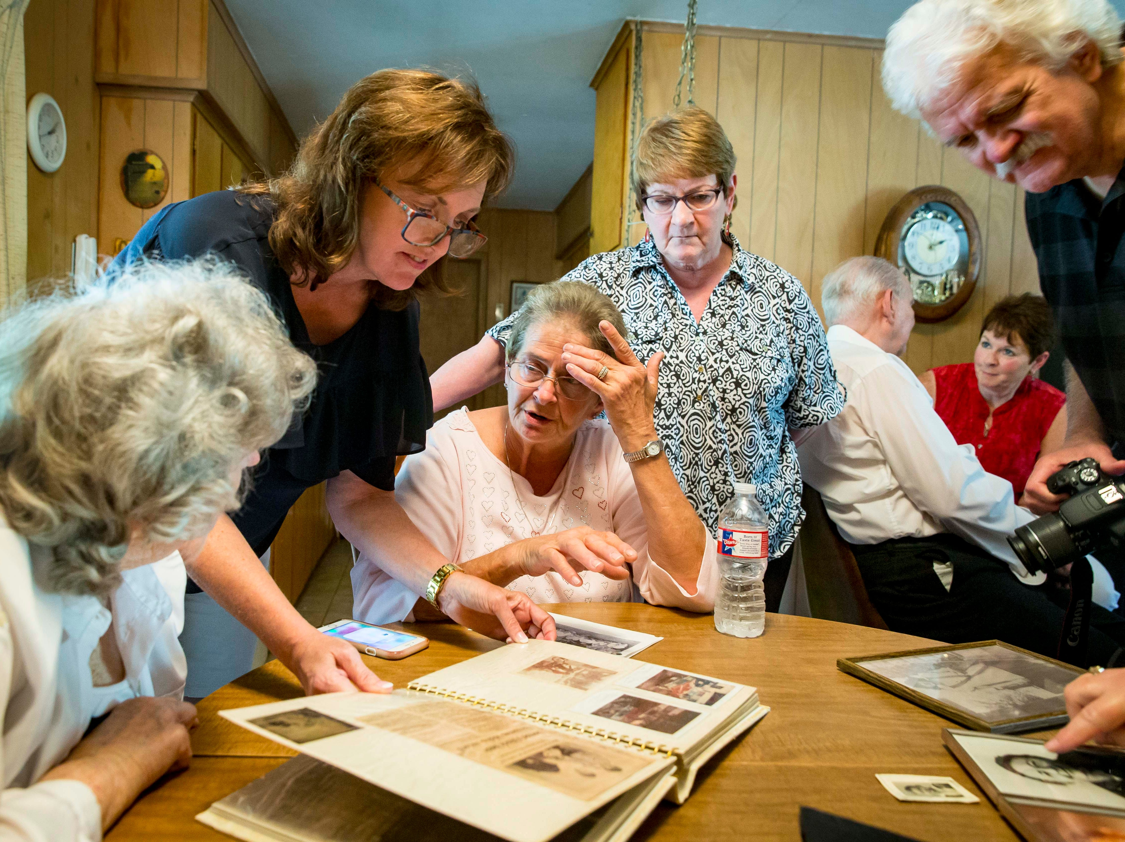 "Hellen Sexton, left, looks over photo albums with children of A.W. ""Dub"" Barron at a family reunion in Tyler, Texas, Sunday, Sept. 2, 2018. Lori Stangl of Omaha, Nebraska, standing left, Dena Simon, hand to head, of Delmont, Pennsylvania, with her half-sister Linda, and Michael Banks of Des Moines, top right. In background are Bobby Sexton with Connie Hoye of Kansas City, Missouri."