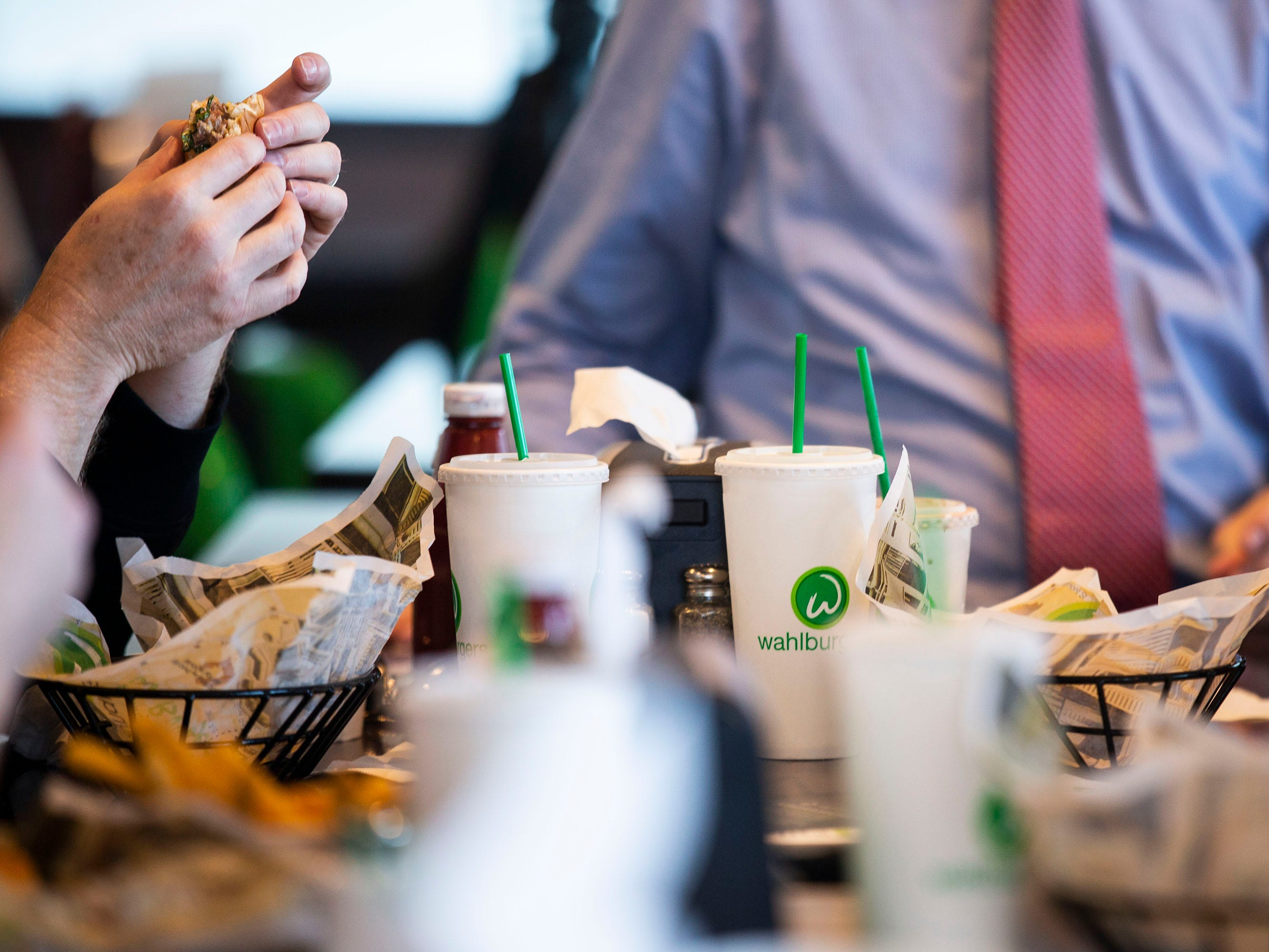 Customers munch on food from Wahlburgers during a preview event for the restaurants opening on Monday, Sept. 10, 2018, in the Jordan Creek Town Center in West Des Moines.