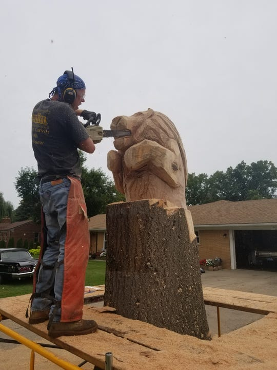 Scott Kuefler of Chesterfield carves a Detroit Lions statue in front of Carl Smith's home in Southfield on Sept. 9, 2018.