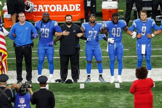 From left, Detroit Lions offensive coordinator Jim Bob Cooter, running back LeGarrette Blount (29), head coach Matt Patricia, safety Glover Quin (27), linebacker Jarrad Davis (40), and quarterback Matthew Stafford (9) lock arms during the national anthem before the Jets game at Ford Field in Detroit, Monday, Sept. 10, 2018.