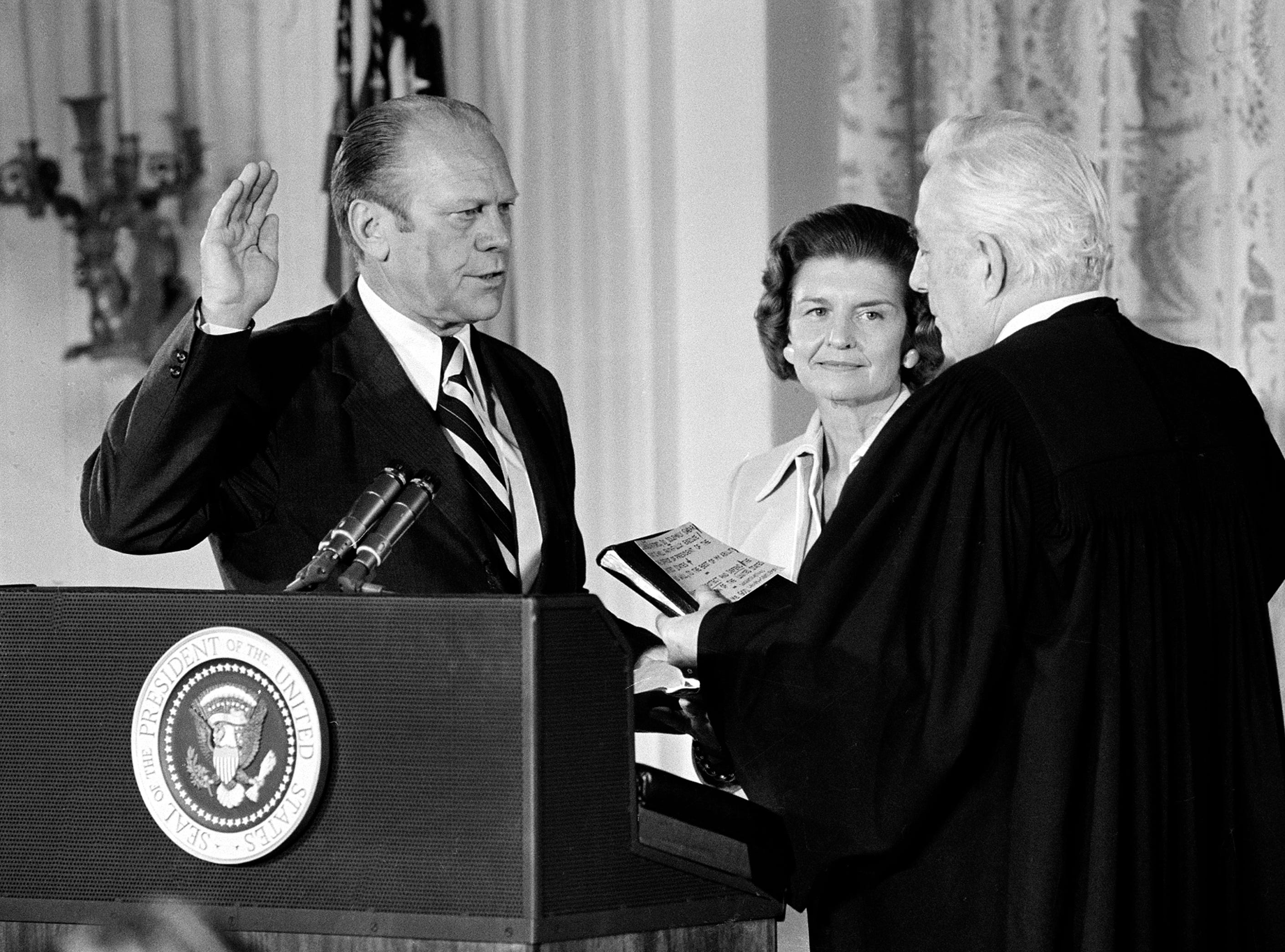 U.S. Chief Justice Warren Burger, right, administers the oath of office to Gerald R. Ford as the 38th President of the United States in the East Room of the White House in Washington, D.C., Aug. 9, 1974. Betty Ford holds the bible at center. Gerald R. Ford, who picked up the pieces of Richard Nixon's scandal-shattered White House as the 38th and only unelected president in America's history