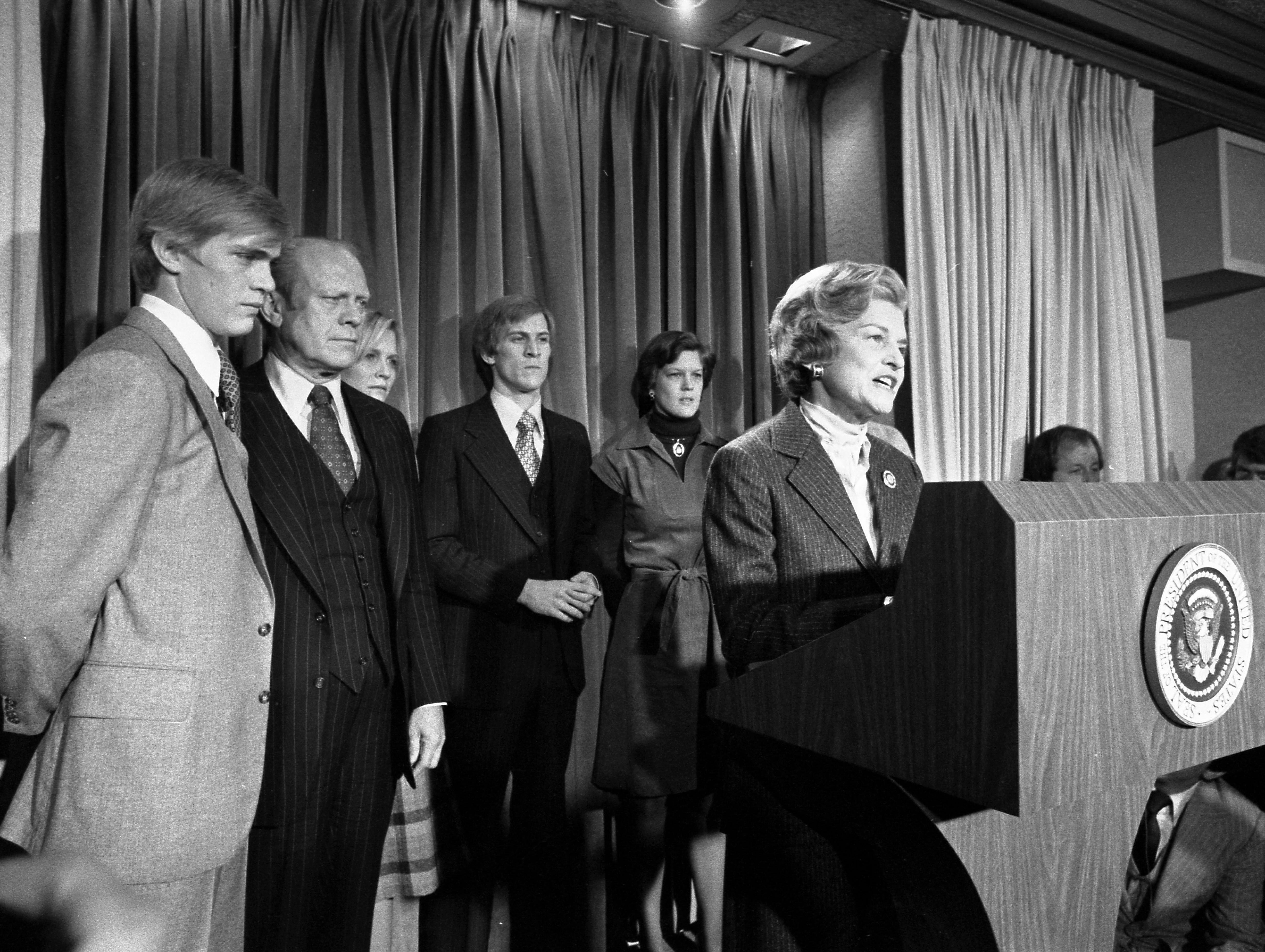 Because President Ford lost his voice in the waning hours of the 1976 presidential campaign, Betty stepped up to read his concession speech to the press. From left, Steve Ford, President Ford, Susan Ford, Mike and Gayle Ford, Betty Ford (at podium).