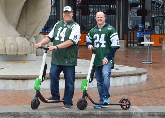 Jim Reisig, left, and Jason Miller ride lime scooters around downtown Detroit before the Lions' season-opening game against the New York Jets on Monday, Sept. 10, 2018.