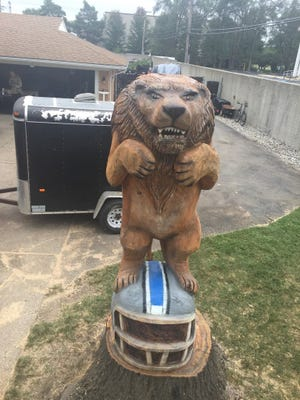 Carl Smith, 55, of Southfield, hired a chainsaw artist to carve an 11-foot statue of a Lion standing on top of a Detroit Lions helmet.