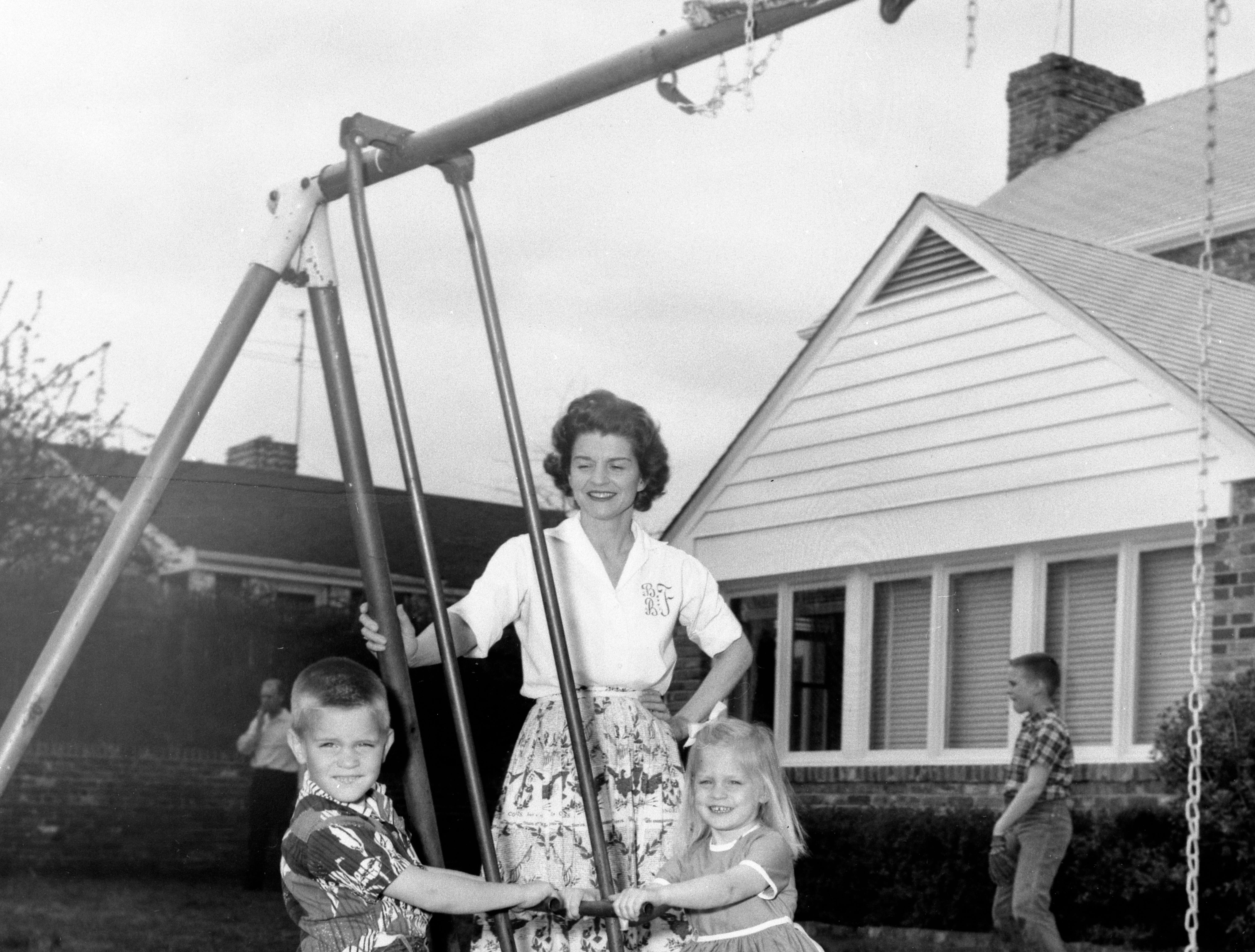 Betty playing with Steve and Susan on the swing set in the backyard of their home on Crown View Drive, as Mike plays ball in the background in 1962.