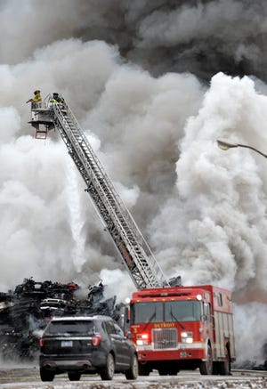 Detroit firefighters battle a two-alarm fire in a recycling yard on Detroit's near east side on January 12, 2018. A new department policy will allow lights and sirens only for emergent runs, instead of all runs.