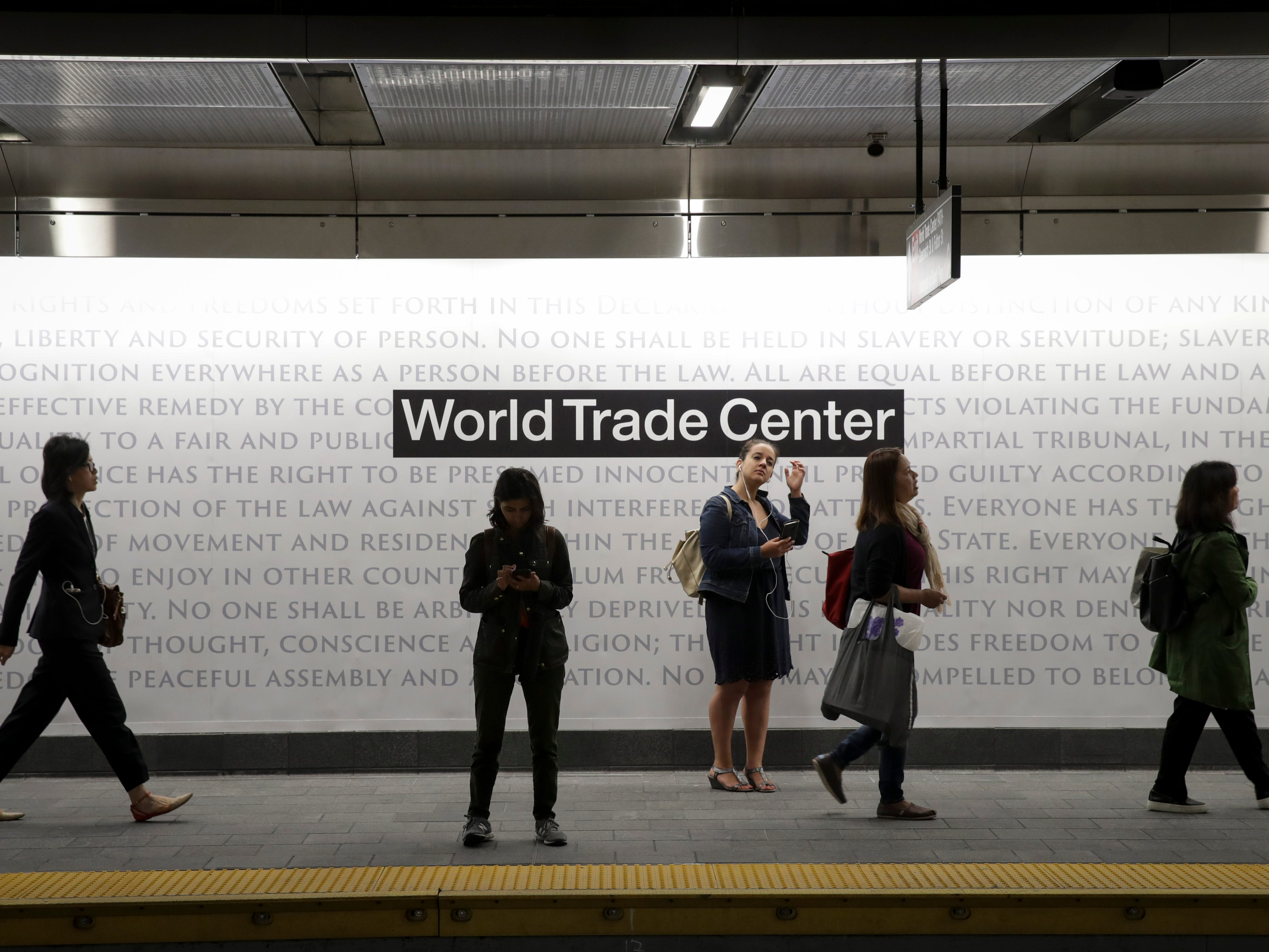 People wait for a train on the platform at the newly opened Cortland Street 1 train station September 10, 2018, in New York City. The train station was buried in debris following the 9/11 terrorist attacks and had been closed since that day 17 years ago.