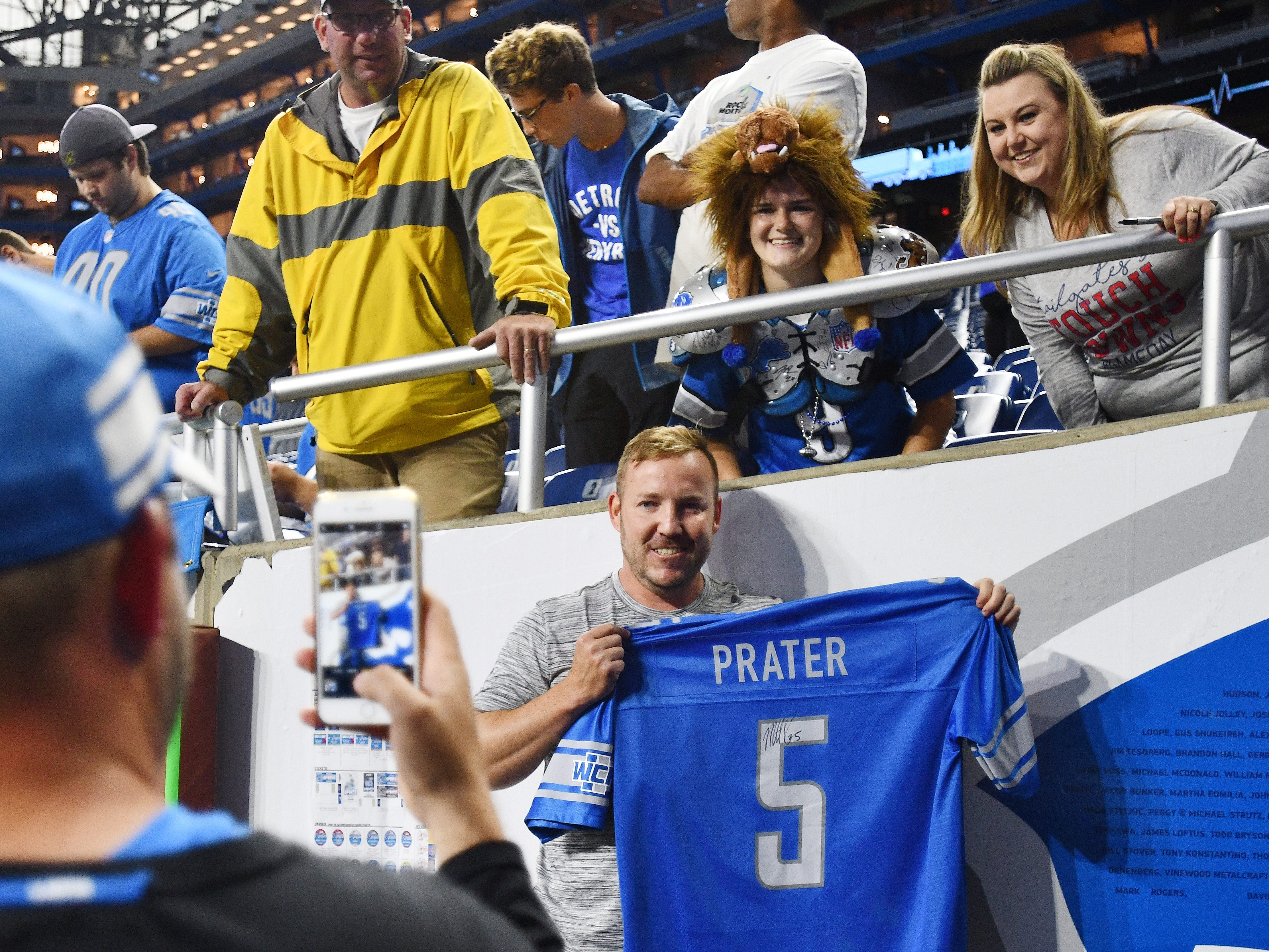 Lions kicker Matt Prater poses for a picture with his jersey for fans after warming up.